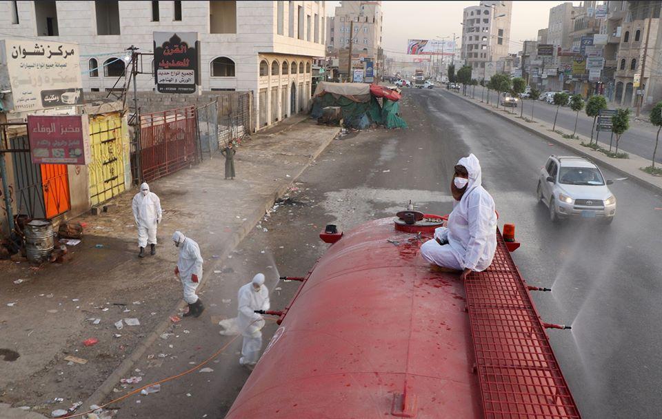 عمال يقومون بتعقيم أحد الشوارع للحد من انتشار كوفيد-19 في صنعاء، اليمن، في 19 مايو 2020.