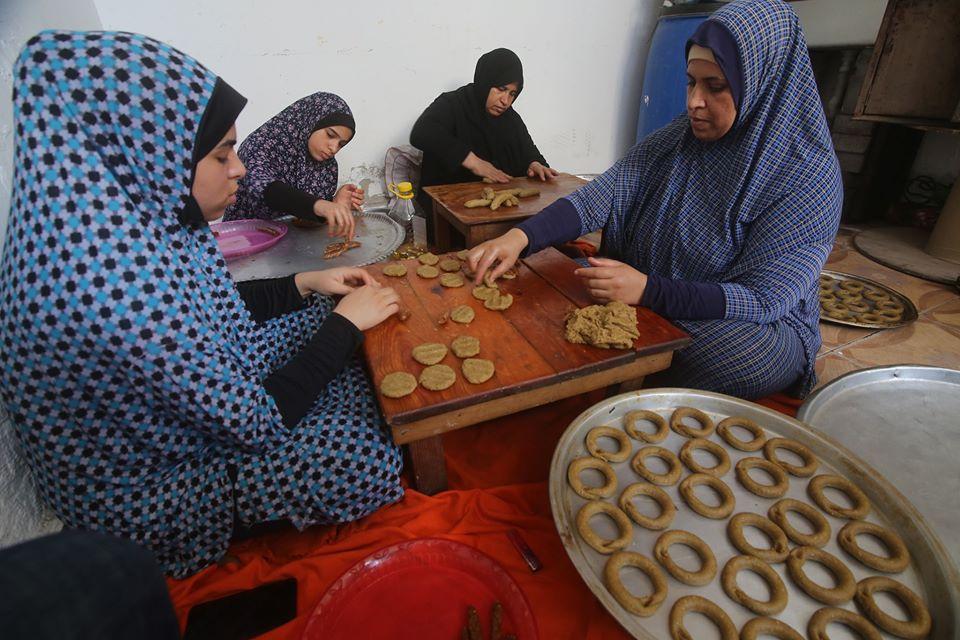 نساء فلسطينيات يعرضن كعكا تقليديا يُصنع قبل عيد الفطر احتفالا بنهاية شهر رمضان المبارك، وذلك خلال أزمة كوفيد-19، في مدينة رفح جنوبي قطاع غزة، في 18 مايو 2020.