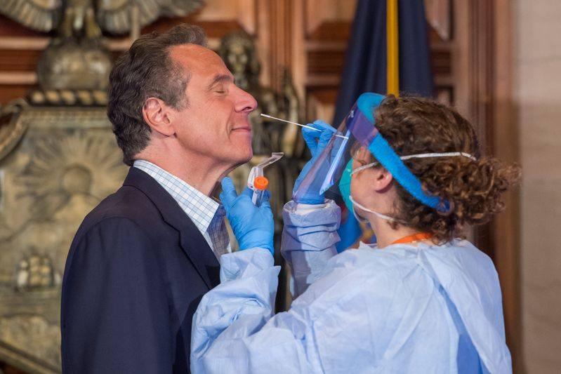 حاكم ولاية نيويورك أندرو كومو (يسارا) يوضح كيفية الحصول على اختبار كوفيد-19 خلال مؤتمر صحفي يومي بشأن #كوفيد-19 في ألباني بولاية نيويورك، الولايات المتحدة، في 17 مايو 2020. وأعلن كومو يوم الأحد أن نيويورك ضاعفت قدرتها لتصل إلى 40000 اختبار يوميا، مشجعا سكان نيويورك المؤهلين على اختبار كوفيد-19.