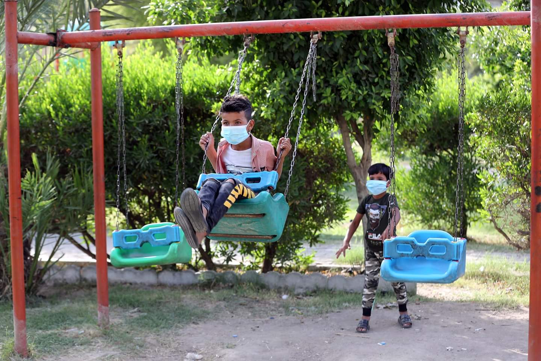 طفل عراقي يلهو على أرجوحة مرتديا قناع الوجه في بغداد، العراق، في 27 مايو 2020. وأعلنت وزارة الصحة يوم الأربعاء تأكيد ما مجموعه 5135 حالة إصابة بكوفيد-19 منذ تفشي المرض في البلاد مع وفاة 175 حالة.
