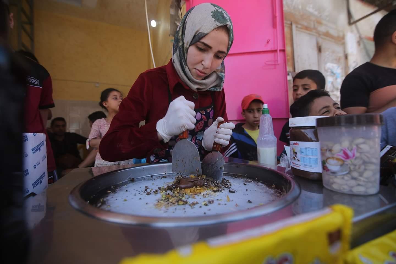 الشابة الفلسطينية فاطمة الزطمة تحضر لفات الآيس كريم في محلها للآيس كريم في مدينة رفح جنوبي قطاع غزة، 31 مايو 2020.