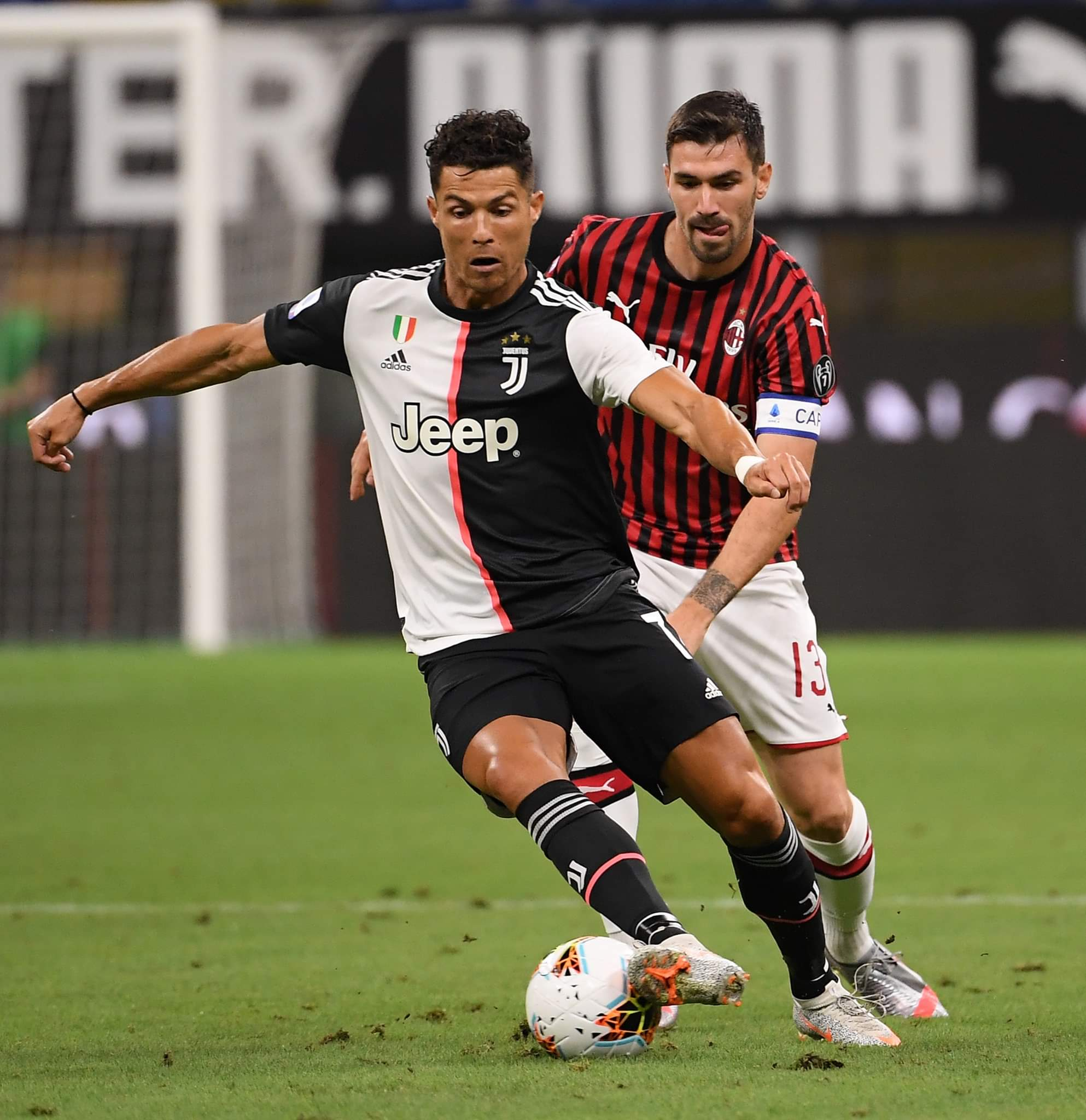 نجم نادي يوفنتوس الإيطالي كريستيانو رونالدو يسيطر على كرته بينما يطارده قلب دفاع نادي ميلان أليسيو رومانيولي خلال المباراة، التي جمعت الفريقين في ميلان يوم 7 يوليو 2020، ضمن مبارايات بطولة الدوري الإيطالي لكرة القدم. وانتهت المباراة بفوز ميلان بنتيجة 4-2.