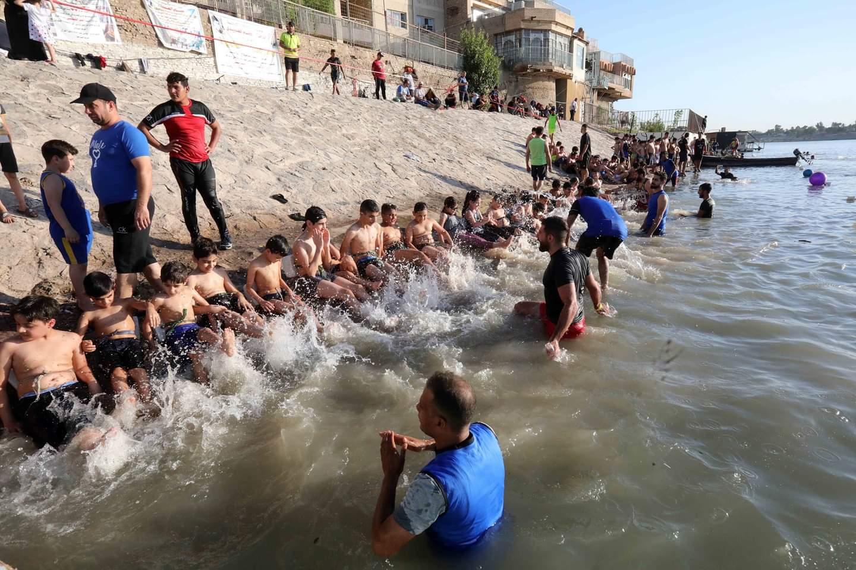 أطفال عراقيون يتعلمون السباحة في نهر دجلة بالعاصمة العراقية بغداد، يوم 24 أغسطس 2020، بعد أن خففت السلطات مؤخرا قيود مكافحة مرض فيروس كورونا الجديد (كوفيد-19).