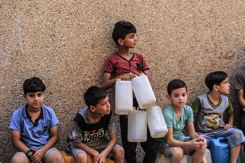 أطفال ينتظرون ملء عبوات بلاستيكية بمياه الشرب من محطة لتحلية المياه في مخيم جباليا للاجئين في شمال قطاع غزة يوم 24 أغسطس 2020. ويشكو الفلسطينيون من انقطاع المياه بسبب أزمة انقطاع التيار الكهربائي في قطاع غزة المحاصر بعد أن أوقفت محطة توليد الكهرباء الوحيدة في القطاع عملها بشكل كامل بسبب نقص الوقود.