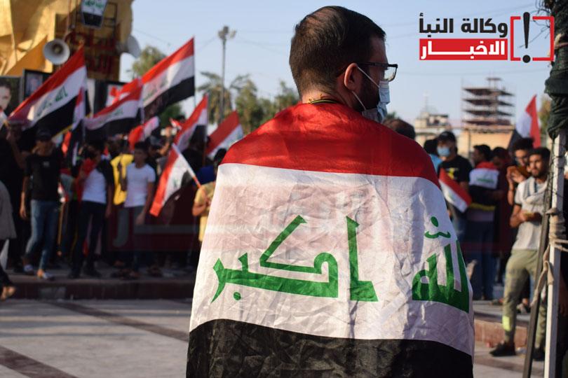 متظاهر يضع العلم العراقي على كتفيه