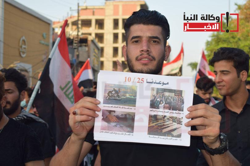 متظاهر يرفع شعارا يتوعد به الحكومة