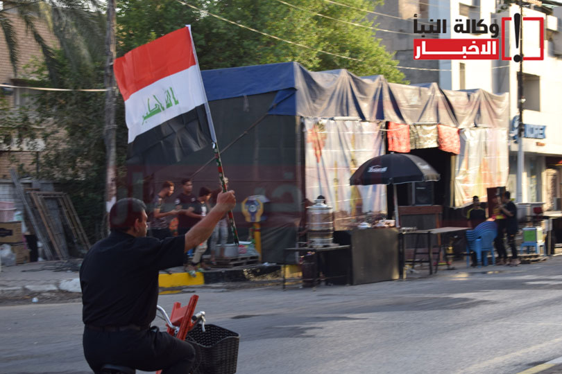 متظاهر يحمل العلم العراقي
